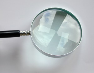 Reflections in the lens of a small round metal magnifying glass for visual enlargement over a light grey background